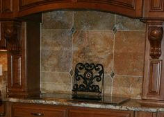 "This tile backsplash features Scabos 16"" Limestone tile cut down to size. We have also incorporated granite clips made from remnant pieces of Lapidus granite,"
