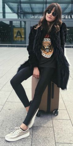 Michelle's travel style + leather leggings + classic Ramones band tee + oversized faux fur coat + Michelle + metallic sneakers + edgy but effective travel outfit. Coat: Gorski Outerwear, Trainers: Tretorn.
