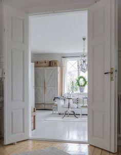 Drewniane drzwi i podłogi w białym salonie