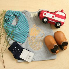 Boys will be boys. Newborn baby boy gift hamper featuring lots of fashion essentials, long sleeve tee by Wilson and Frenchy, stylish bandana bib, socks, leather bootiemoccs and a fire engine rattle. Product photography and flatlay inspiration.