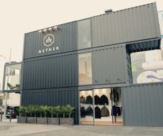 """Aether sells (men's?) clothing (just jackets?) online. They built this store in San Francisco out of three shipping containers stacked, staggered to show off their styles. They wanted the building to embody their style: industrial """"timeless"""".  The store has a custom conveyer system, kind like a dry cleaner; you can see it through the front door, which slides (not swings) open."""