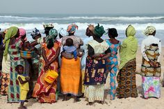 The wives of the fishermen wait for their husbands to bring in the daily catch.- Senegal
