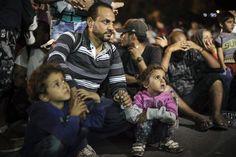 Un padre sirio y sus hijos espera para subir al ferry en la isla griega de Lesbos.