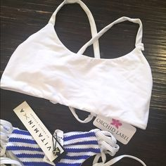NWT White Sporty Bikini Top NWT never worn. Has a small defect where the strap connects (image 4) but if you know how to do basic sewing it's easy to fix! Super cute and sporty in style. Great support for bigger busts. Swim Bikinis