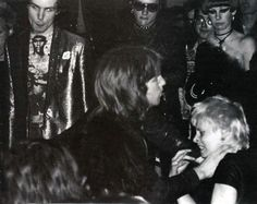 "Sid Vicious and Dave Vanian watching Vivienne Westwood getting beaten at a Sex Pistols show 1976. Paul Saint Savage: ""That guy's about to get a beat down in a few seconds from SEX shop workers and friends as well as the band. I read stories that she was antagonizing that dude for having long hair."" Hervé Labyre: "" Westwood started a fight with members of the audience (rumours say it was because she was feeling ""bored"") and that's how things went. McLaren then joined, and the band followed."