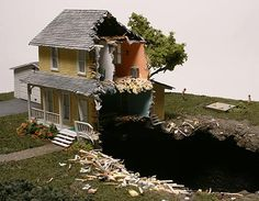 Thomas Doyle creates dioramas that feature tiny hand-painted figures surrounded by domesticity and destruction. Families carry on amidst the debris of disrupted lives, as a whole house hovers above the hole in the ground it used to occupy while a woman greets her folks on the porch. Another home protrudes from a rocky surface, as its dwellers wander the barren landscape above. In yet another disaster, a family is shown in the remains of their abode, the rest of it having left behind a huge…