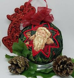 One of a kind Quilted Fabric Christmas Keepsake Ornament - Vintage Santa I! features a vintage Santa from days gone by. Perfect for those that love the Santa's of yesterday!  A pretty green holly and berry design wrap around the outside and a glittering poinsettia is featured on the back.  It is topped with a red bow and hanger. Link in Bio. #OrnamentsByRebecca #NotJustForChristmas #EtsyCIJ2017 #Etsy #EtsySeller #QuiltedFabricOrnaments #Ornaments #handcraftedwithlove #handmade #handmadegifts…