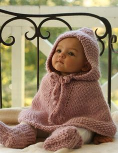 Gorgeous baby in an adorable hooded cape and knit boots.