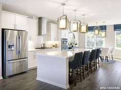 Modern meets practical. A sleek, spacious island paired with textured chairs and beautiful hanging pendants make this kitchen pop. | Pulte Homes
