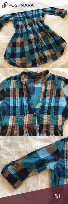 BOGO Free!! Plaid button up 3/4 sleeve tunic A blue and brown plaid button up tunic from Fire. The tunic buttons up the front. The sleeves are 3/4 sleeves that are folded and button at the end. The top have the tunic is pleated. The tunic ties in the back. Armpit to armpit is 17 inches. Sleeve length is 9 inches. Top to bottom is 28.5 inches. Waist is 14.5 inches. Fire Los Angeles Tops Tunics