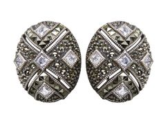 These lovely Judith Jack clip earrings showcase button style with an abstract artsy design in sterling silver and glitzy rhinestones, accented by marcasite.