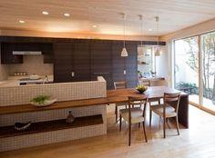 ブラックウォールナットのテーブルと一体の横型対面キッチン。 キッチン アイランド インテリア カウンター タイル ダイニング おしゃれ 壁面収納 ウッド 造作キッチン 