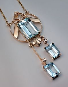 Russian Art Deco Aquamarine Gold Pendant Necklace, Moscow, 1908-1917. The 14K rose and yellow gold openwork negligee pendant features three emerald cut cool blue aquamarines.