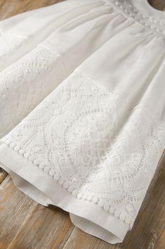 Μένη Ρογκότη - Βαπτιστικά ρούχα για κορίτσι της Maria Zeaki φόρεμα από λευκό λινό ύφασμα με υπέροχη φάσα από βαμβακερή δαντέλα και τρέσα πομ-πομ στο μπούστο