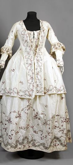 "Gown of white silk, 1770, Sweden, embroidered with darker and lighter purple silk and silver. Consists of seven parts, skirt (width 284 cm), bodice (2 parts), jacket with watteau pleat in the back, 2 loose sleeves and headpiece. Belonged to ""Aunt Ulla"" Ulrica Christina Cronstedt (1756 - 1841) on Gärdesta. Sörmlands museum"