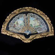 Lot #60: Brise Pearl Fan  DESCRIPTION:Lace fan with pearl sticks and ribs. features a handpainted scene of a Victorian man laying down in a tropical landscape, waving towards his wife swinging from a tree. Finished with gilt trim along the pearl ribs and sticks and is encased in a dore wooden floral motif frame.  CIRCA:20th ORIGIN:Italy DIMENSIONS:H:16.5″ L:23.5″ W:3″