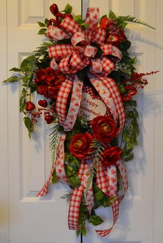 """This Valentine's Day wreath says that love and romance is in this home. It is beautiful with red hydrangeas, roses, and a red anemone flower in the spotlight. They are surrounded with lots of greenery and to top this wreath is a beautiful sign """"Happy Valentine's Day"""". The ribbon in the wreath is wired and will be sure to hold its shape."""