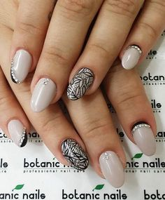 Black French tip inspired nail art and leaf patterns on an off white base for sophistication. Add on diamonds for more accent.