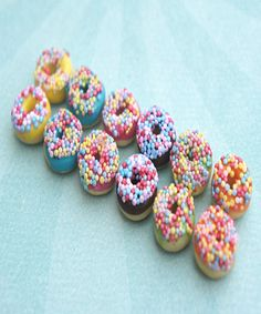 These handmade donut earrings topped with colorful candy sprinkles are sculpted from polymer clay. Each donut measures about 1 cm in diameter and is securely attached to a nickel free silver tone post