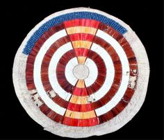 "This is a round wearing blanket medallion  patch showing excellent porcupine quill work  and beaded pinwheel design from the Sioux  Native American Indians circa 1890. The piece  has some quill and bead loss and is on an Indian tanned hide. The piece has early dark  blue glass trade seed beads and ocher dyed  porcupine quill work. This would have been  applied to a wearing blanket and is a  scarcely seen piece. Measures 6.25""x6""."