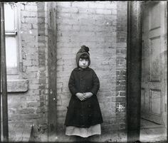 """""""I Scrubs"""" - Katie who Keeps House in West Forty-ninth Street, New York, 1892.""""9 Yr-old Katie at the 52nd Street Industrial School, he asked what kind of work she did, & she answered, 'I scrubs.' Katie & her 3 older siblings took their own flat after their mother died & their father remarried. The older children worked in a hammock factory, & Katie kept house. When asked if she would pose for this picture, which showed in """"Children of the Poor"""" Katie got up, without a question & without a smile."""