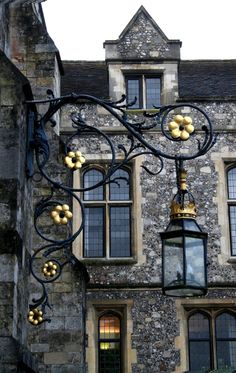 Winchester Lantern attached to wrought iron bracket with flourishes & curlicues that are studded with metal flowers.
