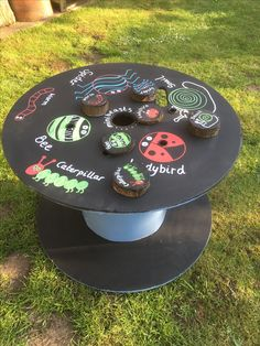 Cable reel with mini beast theme. Mini beasts drawn on with chalk pens so theme can be changed. Children can mark make on the blackboard painted areas.