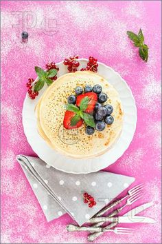 Photo of Overhead shot of pancakes with soft red fruits.