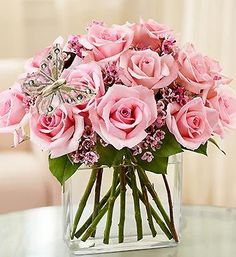 Surprise her (or any Mom you know) with this contemporary spin on the traditional dozen roses. Stunning pink roses, gathered by our florists in a chic rectangular glass vase and accented with a fashionable butterfly pick.