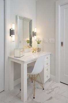 White master bathroom is completed with an Eames Molded Plastic Chair placed on marble porcelain floor tiles in front of a white dressing table accented with brass and glass hardware and marble porcelain countertop.