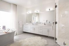 a flawless white bathroom design with classy floating cabinet and sinks with frameless mirror also glass showering room and modern bathtub with appealing wall lighting and fur rug