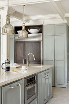 Love the cabinetry color in this kitchen by Tobi Fairley! It's Sherwin Williams Topsail SW 6217.