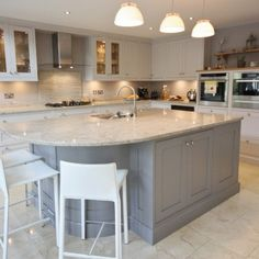 Grey shaker kitchen, white worktops, white pendants, white bar stools.