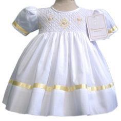 Girls timeless classic white smocked dress with yellow sating ribbons and hand smocking in the full chest, lined. 3 months to 10 y. 17897