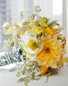 bouquet of acacia, seeded eucalyptus, pincushion protea, dahlias, ranunculus, daffodils, anemones, sweetpeas, jasmine, star of Bethlehem, leucadendron, kangaroo paws, pieris Japonica, and craspedia