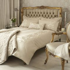 the empress has a cream colored bed with brocade coverings and a golden frame