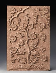 A Mughal red sandstone Architectural Panel Northern India, 17th Century of rectangular form, carved in relief with a flowering eclipta alba (bhringaraj) plant within a niche