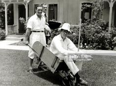 Circa 1930, actor George O'Brien and director John Ford pictured, with John Ford taking a ride in the wheelbarrow.