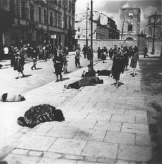 Pedestrians in the Warsaw ghetto walk past corpses lying on the pavement on Rynkowa Street