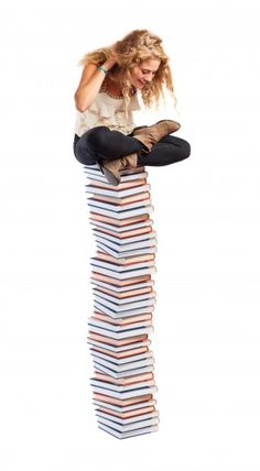 Smiling girl with lots of books Free Photo