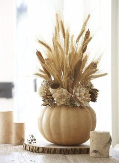 Thanksgiving Arrangement. Use faux pumpkins to create a long lasting and affordable thanksgiving centerpiece arrangement. Via The Daily Basics.
