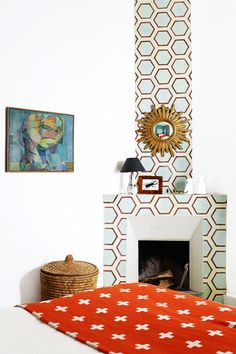 Tour a Pattern-Packed Coastal Bungalow in Morocco // bedroom, orange blanket, hexagonal Popham Design tiles, starburst mirror, fireplace, wicker basket