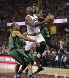 Cleveland Cavaliers' LeBron James, center, drives to the basket against Boston Celtics' Avery Bradley, left, and Amir Johnson in the first half of an NBA basketball game Saturday, March 5, 2016, in Cleveland