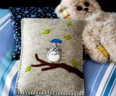 Totoro Kindle case (1/3) - A soft pillow-like Kindle case consisting of wool felt and a lot of yarn. I think she embroidered with yarn! Love the wool felt and use of blanket stitching. Good pattern for the flap (all connected) & button closure.