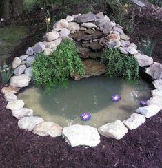 un bassin fait main dans un jardin, bordé de grosses pierres, végétation, idée comment faire une rocaille