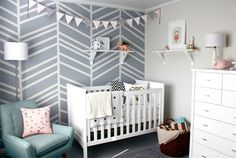nursery with colours neutral, bringing in pops of peach and geometric monochrome as the accents