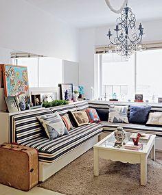 """Uma faixa horizontal de espelho na parede parece alongar o espaço, que ganha """"uma outra janela"""". O sofá em """"L"""" vira duas camas de solteiro para o caso de abrigar visitantes. Projeto do arquiteto Marco Antonio Medeiros"""