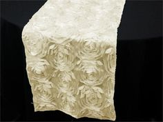 Paradise Rosette Table Runners - Ivory | This parcel from paradise will drift you enchantingly to the empyreal fantasy world of a divine paradise. This mesmeric runner comprises of comely satin roses that pop-out to give an amazingly elegant 3-D effect that is attributed to paradise. The magical glistening flowers are so enticing that will make everyone's jaw drop with fascination. The embossed rose pattern will add flair and character to any drab piece of furniture or dreary decoration…