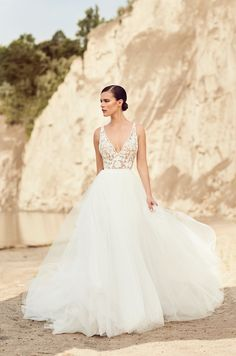 A line gown with soft tulle skirt, textured floral bodice, v neck and criss-cross back.