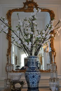 The Enchanted Home. Love the gilded mirror and the blue-and-white jar with branches